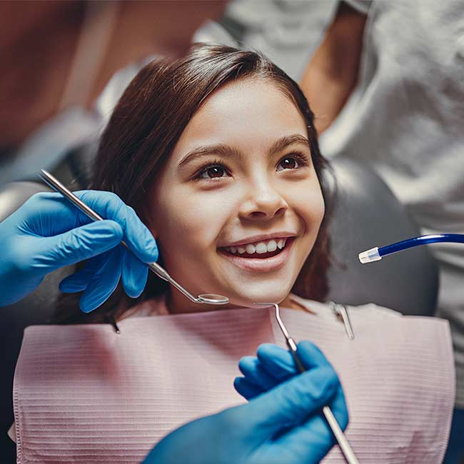 A young girl smiles as a dental progressional with blue glove prepares to use dental tools