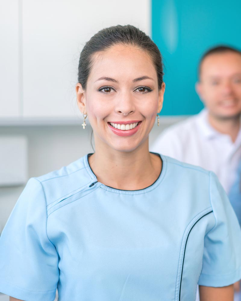 A female dental professional smiles at the camera